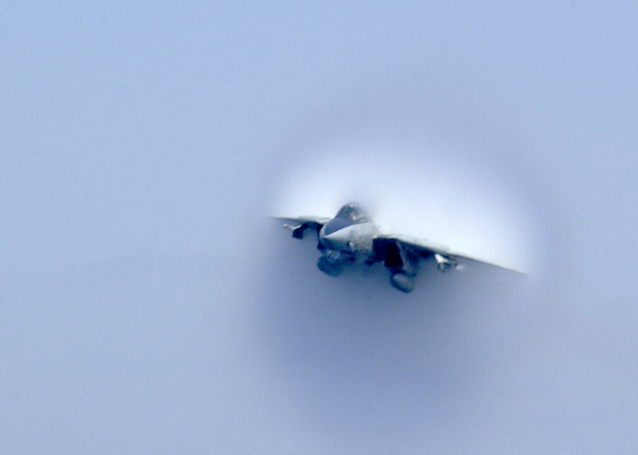 3. United States Navy F-14B Tomcat Fighter Jet. April 22, 2003, Mediterranean Sea. Reaching the sound barrier, breaking the sound barrier: Flying at transonic speeds (flying transonically) -- speeds varying near and at the speed of sound (supersonic) -- can generate impressive condensation clouds caused by the Prandtl-Glauert Singularity. For a scientific explanation, see Professor M. S. Cramer's Gallery of Fluid Mechanics, Prandtl-Glauert Singularity at <http://www.GalleryOfFluidMechanics.com/conden/pg_sing.htm>; and Foundations of Fluid Mechanics, Navier-Stokes Equations Potential Flows: Prandtl-Glauert Similarity Laws at <http://www.Navier-Stokes.net/nspfsim.htm>. Photo Credit: Photographer's Mate Airman Justin S. Osborne, Navy NewsStand - Eye on the Fleet Photo Gallery (http://www.news.navy.mil/view_photos.asp, 030422-N-0382O-588), United States Navy (USN, http://www.navy.mil), United States Department of Defense (DoD, http://www.DefenseLink.mil or http://www.dod.gov), Government of the United States of America (USA).