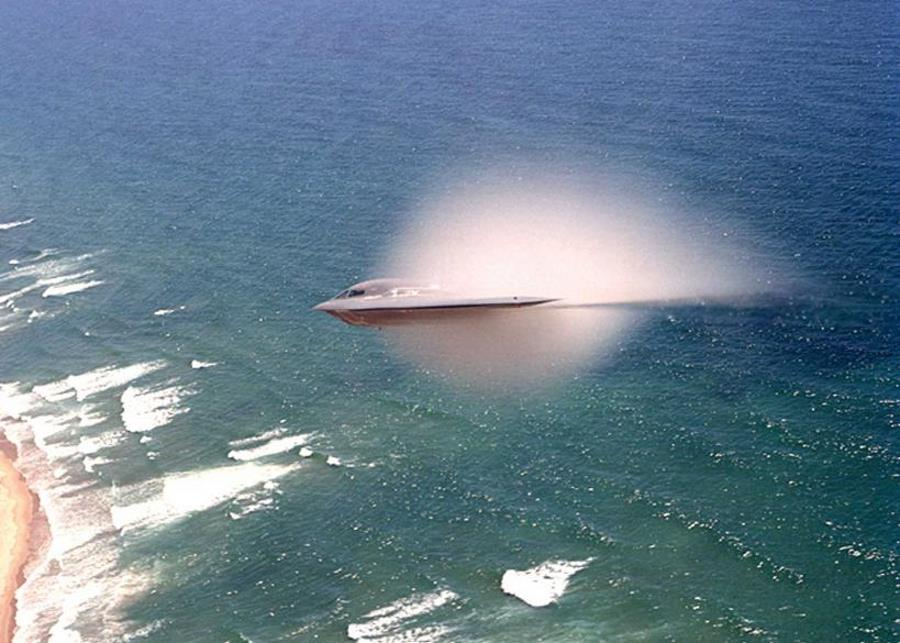 7. A B-2 Spirit Stealth Bomber, United States Air Force, Pacific Ocean. Reaching the sound barrier, breaking the sound barrier: Flying at transonic speeds (flying transonically) -- speeds varying near and at the speed of sound (supersonic) -- can generate impressive condensation clouds caused by the Prandtl-Glauert Singularity. For a scientific explanation, see Professor M. S. Cramer's Gallery of Fluid Mechanics, Prandtl-Glauert Singularity at <http://www.GalleryOfFluidMechanics.com/conden/pg_sing.htm>; and Foundations of Fluid Mechanics, Navier-Stokes Equations Potential Flows: Prandtl-Glauert Similarity Laws at <http://www.Navier-Stokes.net/nspfsim.htm>. Photo Credit: Bobbi Garcia, News - Archive (http://www.edwards.af.mil/archive, January 10, 2003, Edwards photographer awarded first place in photo contest), Air Force Flight Test Center, Edwards Air Force Base (http://www.edwards.af.mil), United States Air Force (USAF, http://www.af.mil), United States Department of Defense (DoD, http://www.DefenseLink.mil or http://www.dod.gov), Government of the United States of America (USA).