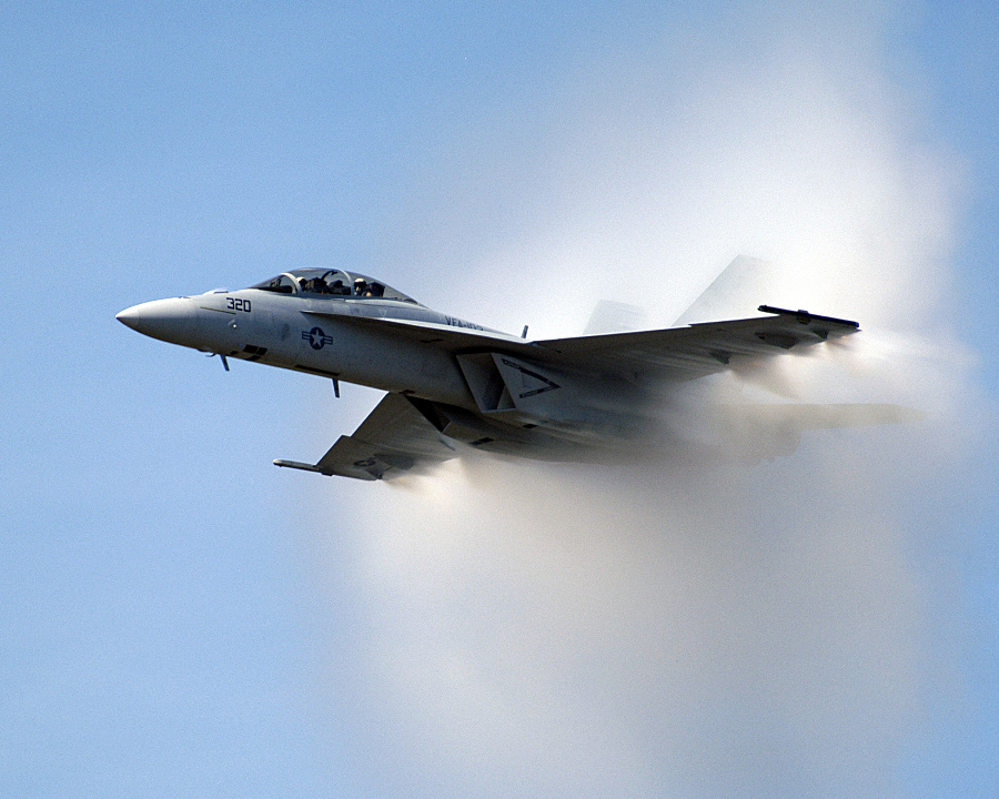 9. An F/A-18F Super Hornet Fighter Jet, September 25, 2004. United States Navy. Naval Air Station Oceana, Commonwealth of Virginia, USA. Reaching the sound barrier, breaking the sound barrier: Flying at transonic speeds (flying transonically) -- speeds varying near and at the speed of sound (supersonic) -- can generate impressive condensation clouds caused by the Prandtl-Glauert Singularity. For a scientific explanation, see Professor M. S. Cramer's Gallery of Fluid Mechanics, Prandtl-Glauert Singularity at <http://www.GalleryOfFluidMechanics.com/conden/pg_sing.htm>; and Foundations of Fluid Mechanics, Navier-Stokes Equations Potential Flows: Prandtl-Glauert Similarity Laws at <http://www.Navier-Stokes.net/nspfsim.htm>. Photo Credit: Photographer's Mate 2nd Class Daniel J. McLain, Navy NewsStand - Eye on the Fleet Photo Gallery (http://www.news.navy.mil/view_photos.asp, 040925-N-0295M-108), United States Navy (USN, http://www.navy.mil), United States Department of Defense (DoD, http://www.DefenseLink.mil or http://www.dod.gov), Government of the United States of America (USA).