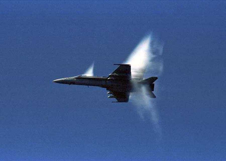7. An F/A-18 Hornet Fighter Jet, United States Navy, Off the Coast of Japan, Sea of Japan. Reaching the sound barrier, breaking the sound barrier: Flying at transonic speeds (flying transonically) -- speeds varying near and at the speed of sound (supersonic) -- can generate impressive condensation clouds caused by the Prandtl-Glauert Singularity. For a scientific explanation, see Professor M. S. Cramer's Gallery of Fluid Mechanics, Prandtl-Glauert Singularity at <http://www.GalleryOfFluidMechanics.com/conden/pg_sing.htm>; and Foundations of Fluid Mechanics, Navier-Stokes Equations Potential Flows: Prandtl-Glauert Similarity Laws at <http://www.Navier-Stokes.net/nspfsim.htm>. Photo Credit: Seventh Fleet - Photos (http://www.c7f.navy.mil/images.html, November 12, Sea of Japan), Commander, U.S. Seventh Fleet (http://www.c7f.navy.mil), United States Navy (USN, http://www.navy.mil), United States Department of Defense (DoD, http://www.DefenseLink.mil or http://www.dod.gov), Government of the United States of America (USA).