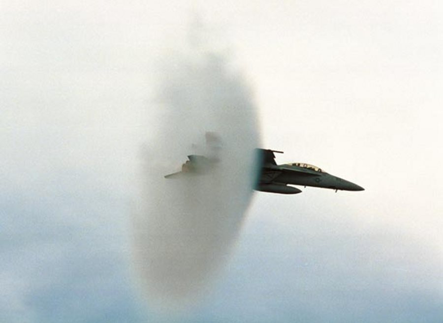8. An F/A-18E Super Hornet Fighter Jet, United States Navy, Off the Coast of Southern California, United States. Reaching the sound barrier, breaking the sound barrier: Flying at transonic speeds (flying transonically) -- speeds varying near and at the speed of sound (supersonic) -- can generate impressive condensation clouds caused by the Prandtl-Glauert Singularity. For a scientific explanation, see Professor M. S. Cramer's Gallery of Fluid Mechanics, Prandtl-Glauert Singularity at <http://www.GalleryOfFluidMechanics.com/conden/pg_sing.htm>; and Foundations of Fluid Mechanics, Navier-Stokes Equations Potential Flows: Prandtl-Glauert Similarity Laws at <http://www.Navier-Stokes.net/nspfsim.htm>. Photo Credit: PHAA Jeremie Kerns, USS Carl Vinson (CVN 70) Photo Gallery (http://www.vinson.navy.mil/photos/oct00.html, October 2000, VFA-122 experts breaking the sound barrier in the F/A 18E), USS Carl Vinson (CVN 70) (http://www.vinson.navy.mil), United States Navy (USN, http://www.navy.mil), United States Department of Defense (DoD, http://www.DefenseLink.mil or http://www.dod.gov), Government of the United States of America (USA).