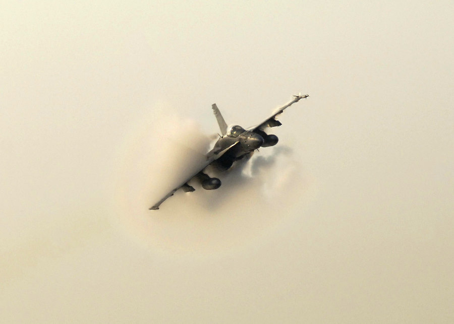 4. An F/A-18 Hornet Fighter Jet, June 9, 2004. United States Navy, Atlantic Ocean. Reaching the sound barrier, breaking the sound barrier: Flying at transonic speeds (flying transonically) -- speeds varying near and at the speed of sound (supersonic) -- can generate impressive condensation clouds caused by the Prandtl-Glauert Singularity. For a scientific explanation, see Professor M. S. Cramer's Gallery of Fluid Mechanics, Prandtl-Glauert Singularity at <http://www.GalleryOfFluidMechanics.com/conden/pg_sing.htm>; and Foundations of Fluid Mechanics, Navier-Stokes Equations Potential Flows: Prandtl-Glauert Similarity Laws at <http://www.Navier-Stokes.net/nspfsim.htm>. Photo Credit: Photographer's Mate 3rd Class Milosz Reterski, Navy NewsStand - Eye on the Fleet Photo Gallery (http://www.news.navy.mil/view_photos.asp, 040609-N-9742R-041), United States Navy (USN, http://www.navy.mil), United States Department of Defense (DoD, http://www.DefenseLink.mil or http://www.dod.gov), Government of the United States of America (USA).